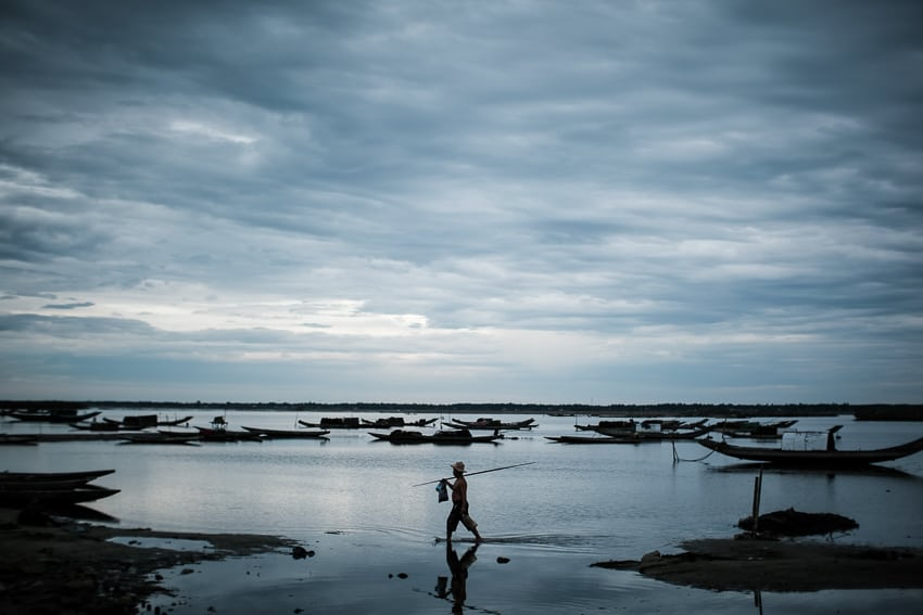 A fisherman holding a rod walks across a bay a low tide with cloudy skies