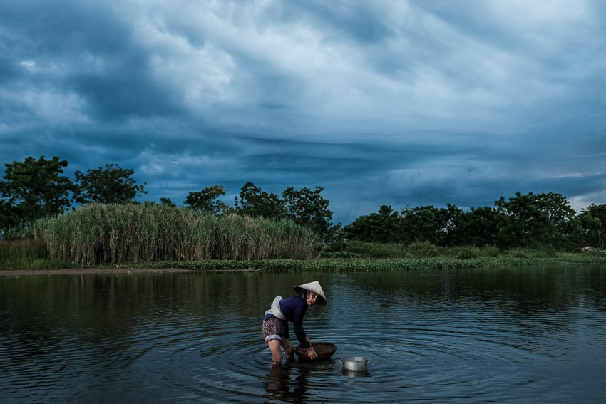On a stormy day we captured a woman gathering snails from the river on our sunset photography tour and workshop