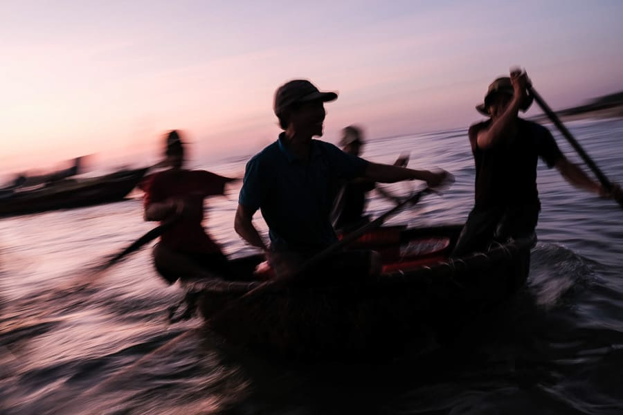 Fishermen surfing the waves on basket boats at sunrise during hoi an advanced photography tour