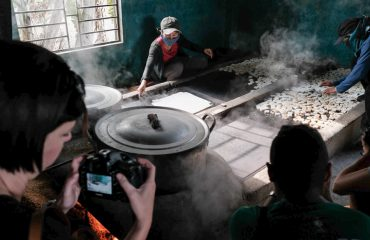 photographers capturing workers in a cake factory in Vietnam