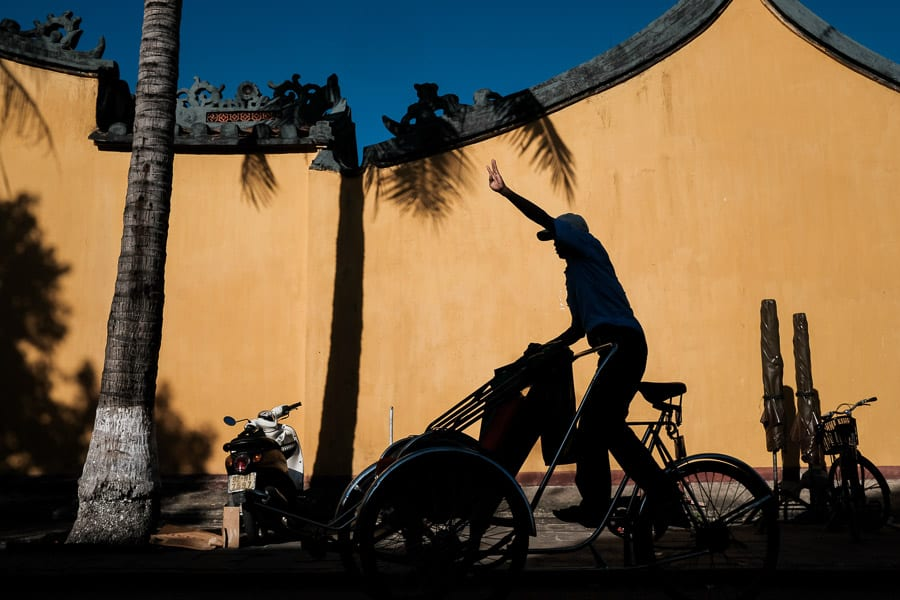 Street Photography - A Man Rides A Rickshaw Though Hoi An Old Town