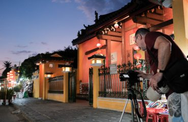 visitor taking a night photo of Hoi An old town