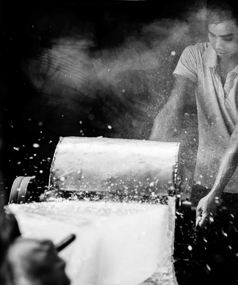 Two men grinding ice blocks in central Vietnam