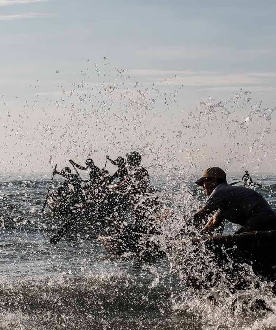 Fishermen braving the waves to unload the fish in central Vietnam