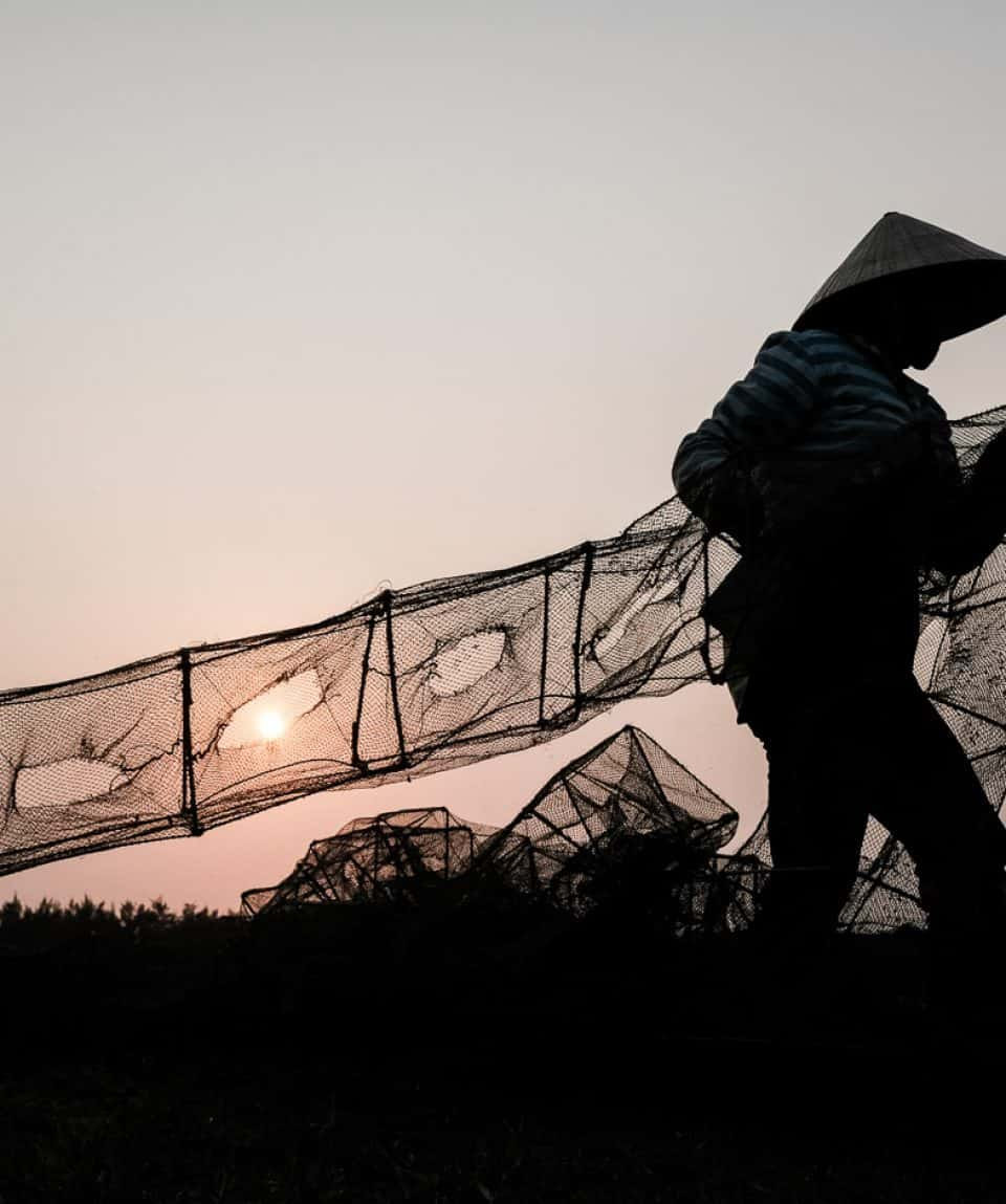 Fisherman in Vietnam pulling a net out of the water at sunrise