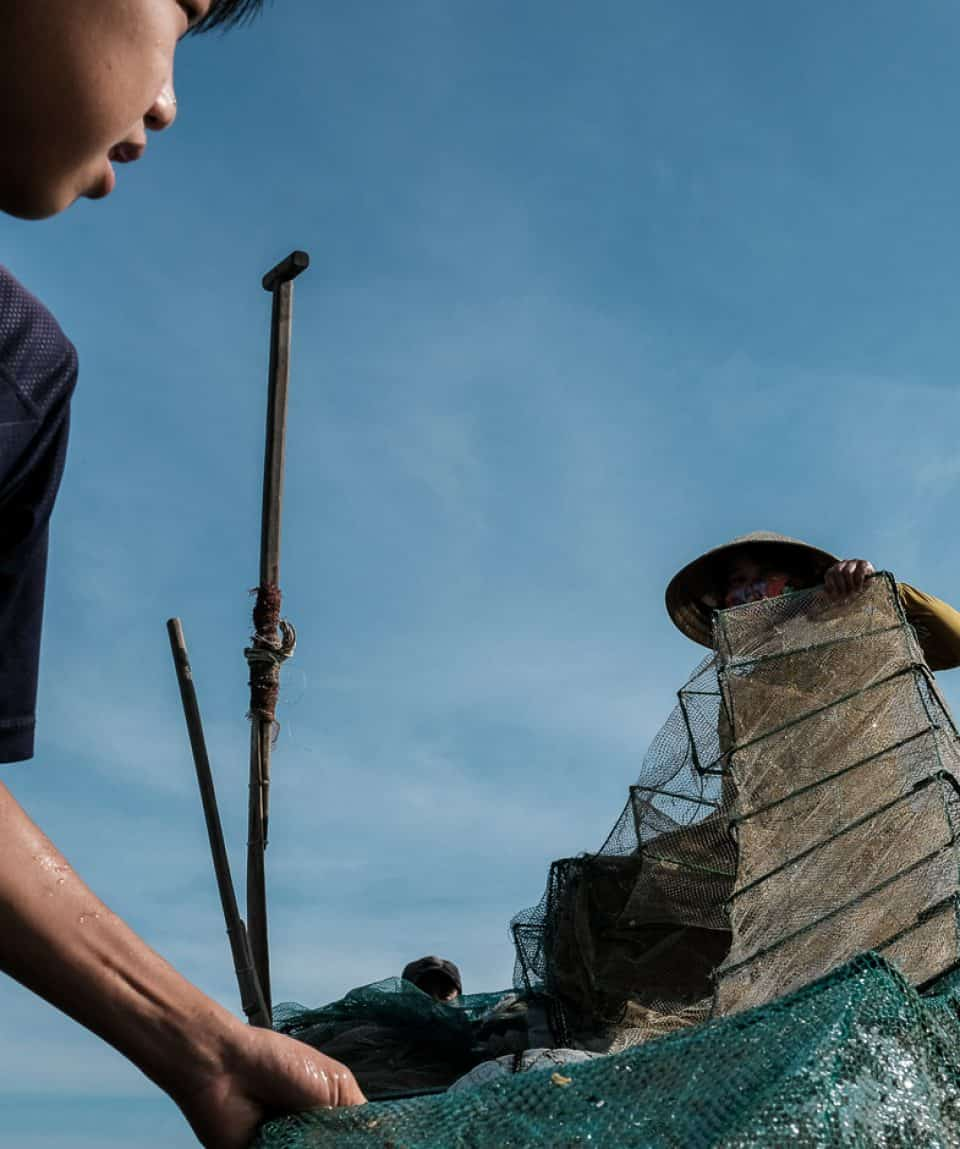 Boy and mum cleaning the fishing net at sunrise in Vietnam