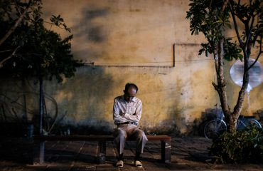 Man sleeping on a bench in Hoi An at night
