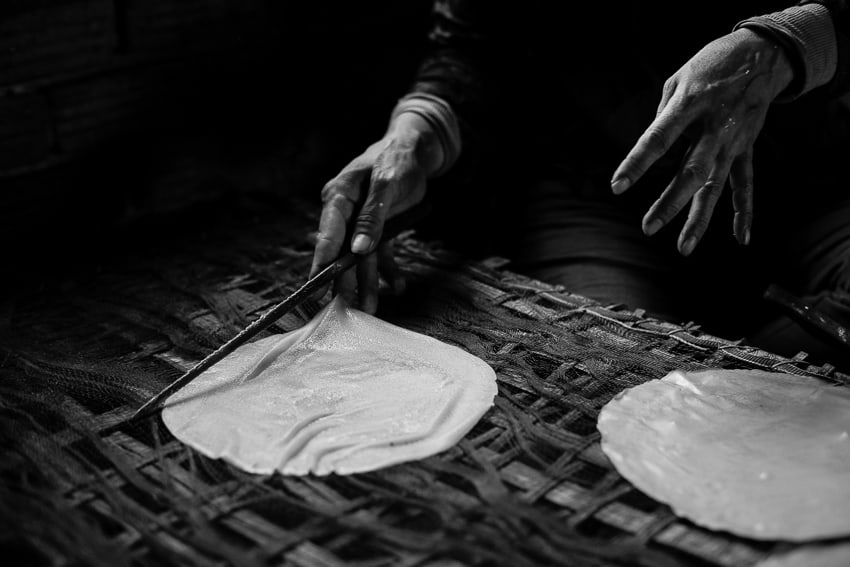Close up of hands cooking banh trang taken during hoi an photo tour and workshop