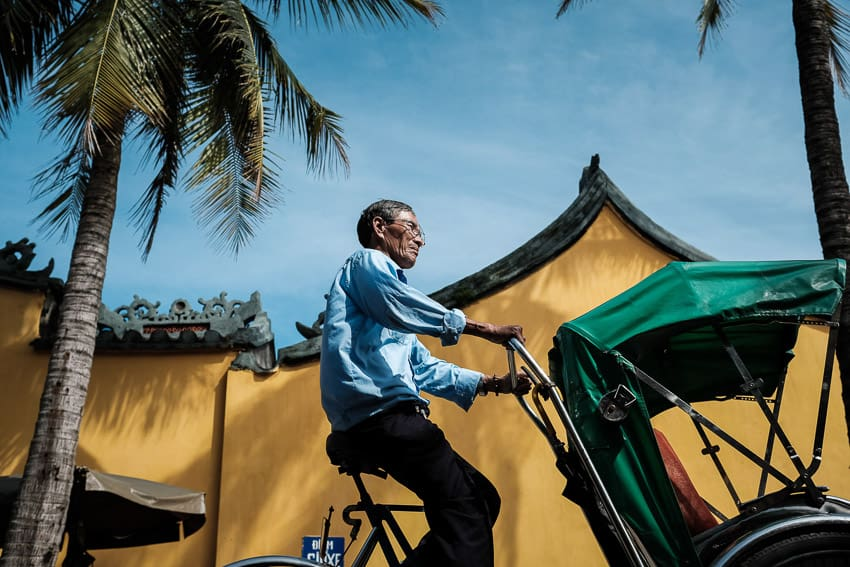 A cyclo driver in front of Hoi an famous yellow wall during a photography tour in Hoi An