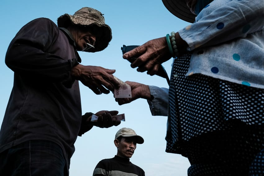 people exchanging money in a makrket in Vietnam during hoi an photo tour