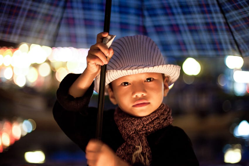 A boy holding an umbrella at night in the old town of Hoi An during hoi an photo tour and workshop