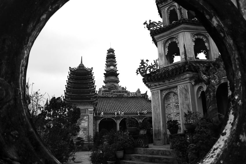 See attractions differently like this pagoda photographed though sculptures on Hoi An Photo Tour