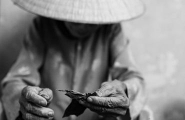 Vietnamese woman rolling a cigar with tobacco leafs